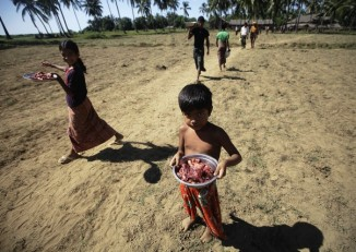 People displaced by ethnic violence in Pauktaw carry meat that is distributed as aid (Reuters)