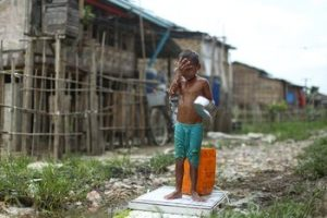 A young boy washes his face in a squatter settlement in Hlaing Tharyar Township in Rangoon which sees regular flooding during monsoon. (Photo: Hkun Lat/ Myanmar Now.)