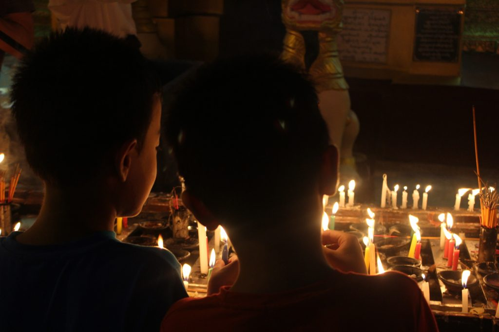 Two children gather in front of the candle display inside Shwedagon Pagoda. (Photo: Libby Hogan / DVB)